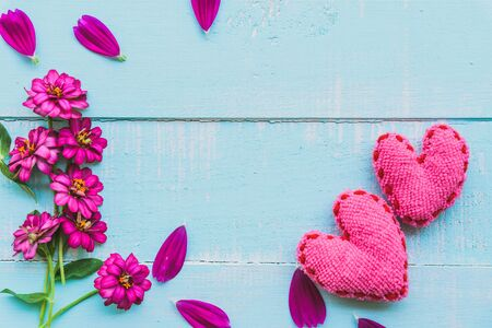 Top view  of pink double click cosmos flower with handmade pink heart on blue and white color wooden background with pastel vintage style. Love, Wedding and Valentines day concept.