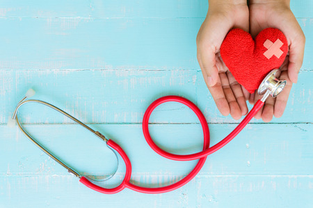 World health day, Healthcare and medical concept. Woman hand holding red heart with Stethoscope, notepad or notebook, thermometer and yellow Pill on Pastel white and blue wooden table background texture.