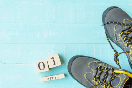 April fools day concept. shoelaces tied together and Wooden block calendar with empty space for text on bright blue and white wooden background. Stock Photo