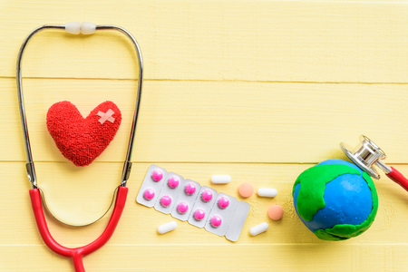 World health day, Healthcare and medical concept. Red heart with Stethoscope, handmade globe, thermometer and yellow Pill on Pastel white and pink wooden background.