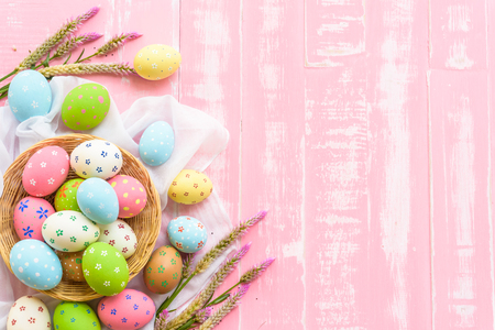 Happy easter! Colorful of Easter eggs in nest with paper star, flower and Feather on pastel color bright pink and white wooden background.