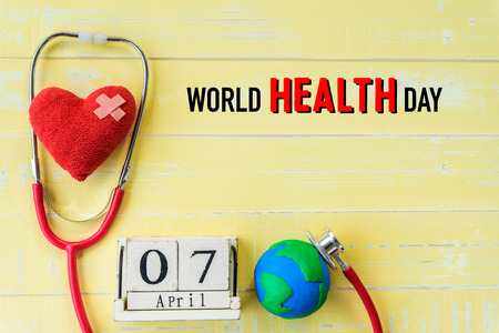 Wooden Block calendar for World health day, April 7. Healthcare and medical concept. Red heart with Stethoscope, handmade globe on Pastel white and blue wooden table background texture.