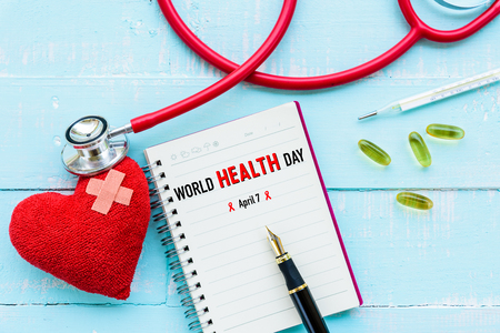 World health day, Healthcare and medical concept. Stethoscope, red heart, notepad or notebook, thermometer and yellow Pill on Pastel white and blue wooden table background texture.
