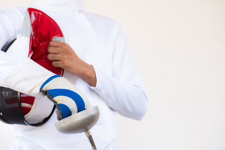 Close-up of a fencer in white fencing suit and holding his mask and a sword on white background