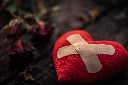First Aid Band Cushioned Plaster Strip Medical Patch glued on red heart with dried red rose on wooden background. Heart broken, Love and Valentines day concept.