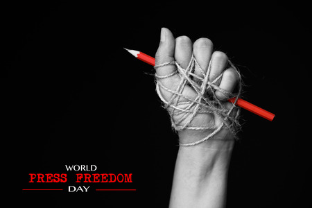 Hand with red pencil tied with rope, depicting the idea of freedom of the press or freedom of expression on dark background in low key. world press freedom day concept. 写真素材