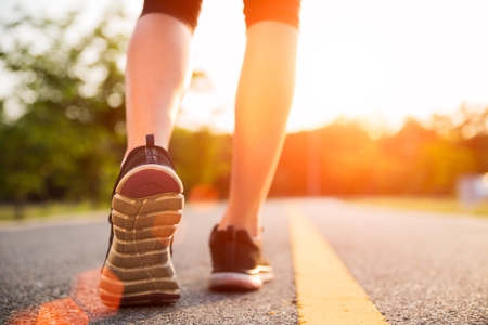 Healthy lifestyle sports woman legs running and walking  while exercising outdoors during sunrise or sunset. Moving forward to success concept. Stock Photo