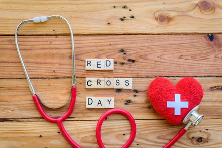 Wooden Block for World Red Cross and Red Crescent day, May 8. Healthcare and medical concept. Red heart with Stethoscope on wooden table background texture.