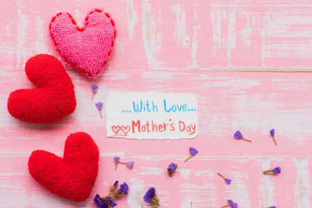 Happy mothers day concept. Top view of Love you MOM text on paper tag with pink handmade heart on bright pink pastel wooden background.