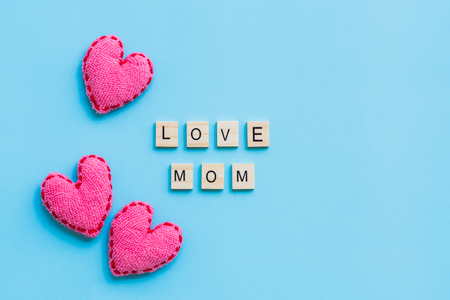 Happy mothers day concept. Top view of LOVE MOM text on wooden block with pink handmade heart on bright blue pastel background.