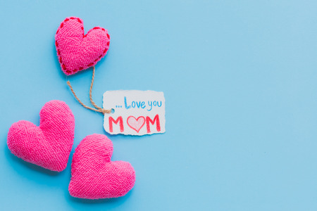 Happy mothers day concept. Top view of Love you MOM text on paper tag with pink handmade heart on bright blue pastel background.