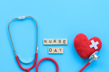 Journée internationale des infirmières, 12 mai. Concept de soins de santé et médical. Coeur rouge à la main avec stéthoscope et bloc de bois jour infirmière sur fond bleu.