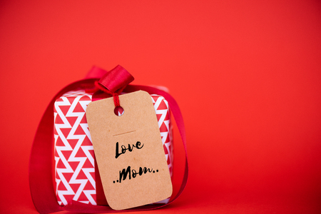 Happy mothers day concept. Gift box with greeting tag on red background.  Christmas, Boxing day  and New year concept. Stock Photo