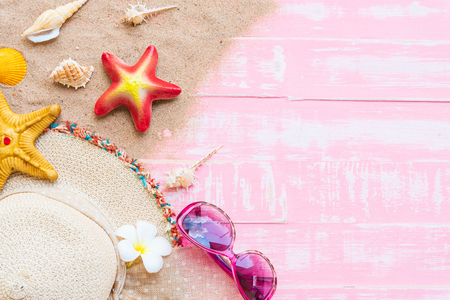 Beach accessories including sunglasses, starfish, hat beach and shell on bright pink pastel wooden background for summer holiday and vacation concept.