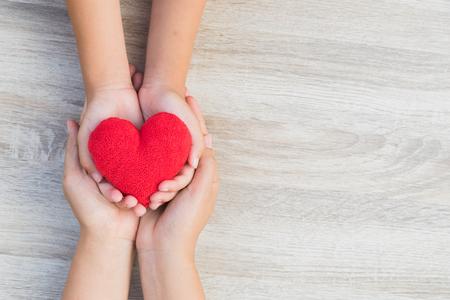 Gezondheidszorg, liefde, orgaandonatie, familiale verzekering en MVO-concept. volwassene en kind handen met handgemaakte rood hart op houten achtergrond. Stockfoto