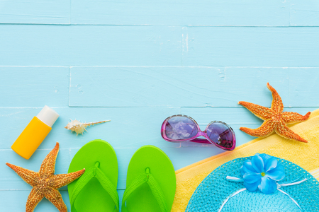 Beach accessories including sunglasses, starfish, hat beach, sunblock, colorful flip flop and shell on bright blue pastel wooden background for summer holiday and vacation concept. Stock Photo