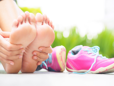 Closeup woman massaging her painful foot while exercising.   Running sport injury concept. Stock Photo