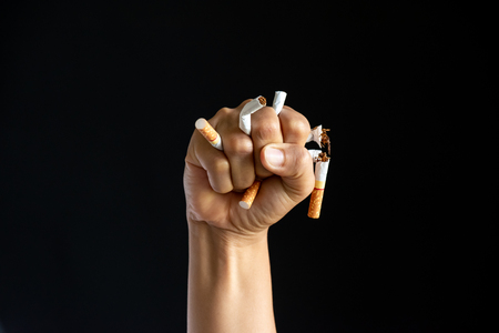 World No Tobacco Day. STOP Smoking. Close up Man hand crushing and destroying cigarettes on black background. Foto de archivo
