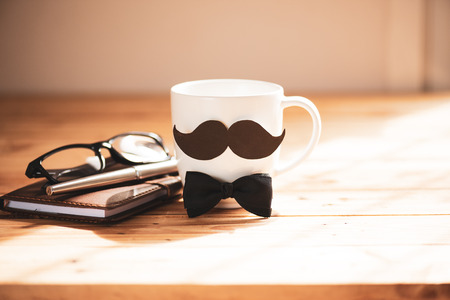 Happy fathers day concept. coffee cup with black paper mustache and pen, note book, glasses on wooden table background. Stock Photo