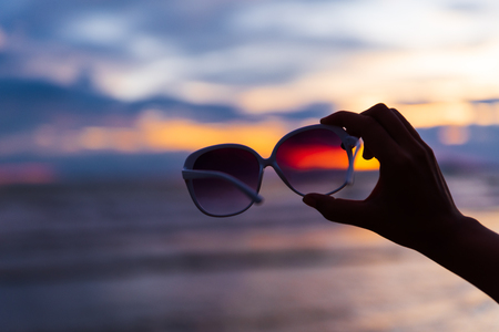 Silhouette woman hand holding sunglasses over sea and Sandy beach in background during sunset for summer holiday and vacation concept. Stockfoto