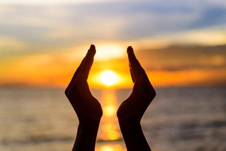 여자 손 일출 또는 일몰 동안 태양을 잡고.