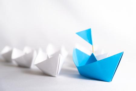 Koncepcja przywództwa. niebieski papierowy statek z flagą prowadzi wśród białych. Jeden statek lidera prowadzi inne statki.