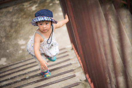 Happy Little Cute Girl Walking Up The Stairs. Kid First Step Concept. Stock  Photo