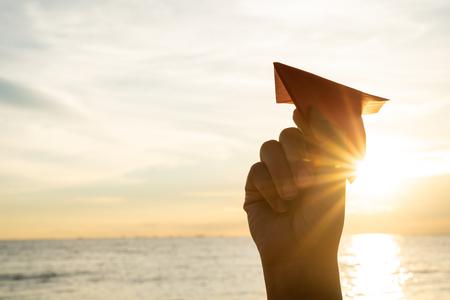 Mano de mujer sosteniendo un cohete de papel rojo con fondo de cielo azul durante la puesta de sol. Foto de archivo