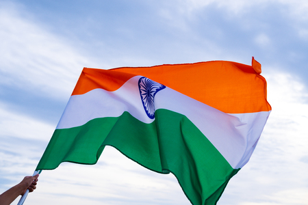 Close up man hand holding India flag on the blue sky background. Indian Independence Day, 15 August. 免版税图像
