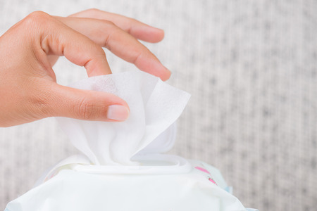 Closeup woman hand holding wet wipes from package. healthcare, people and medicine concept.