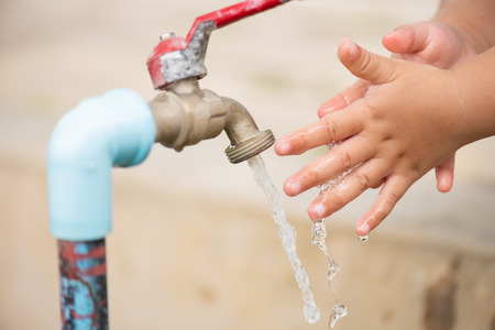 Water pouring in little girls hands. World Water Day concept. Фото со стока