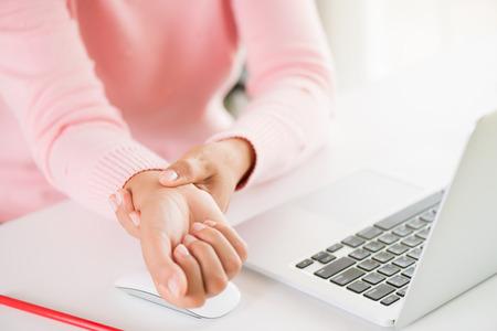 Closeup mujer sosteniendo su dolor de muñeca por usar la computadora. Síndrome de oficina con dolor de manos por enfermedad ocupacional.