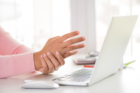Closeup woman holding her wrist pain from using computer. Office syndrome hand pain by occupational disease. Archivio Fotografico