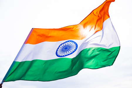 Close up man hand holding India flag on the blue sky background. Indian Independence Day 写真素材