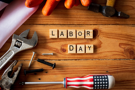 USA Labor day concept, First Monday in September. Different kinds on wrenches, handy tools, America flag and wooden blocks on wooden table. Stock Photo