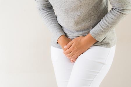 Junge Frau, die schmerzhafte Bauchschmerzen mit Händen hält, die ihren Schrittunterbauch drücken. Medizinische oder gynäkologische Probleme, Gesundheitskonzept