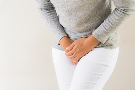 Young woman having painful stomachache with hands holding pressing her crotch lower abdomen. Medical or gynecological problems, healthcare concept Standard-Bild