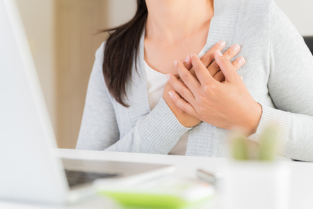 Closeup business woman having heart attack. Woman touching breast and having chest pain after long hours work on computer. Office syndrome, Healthcare And Medical concept.
