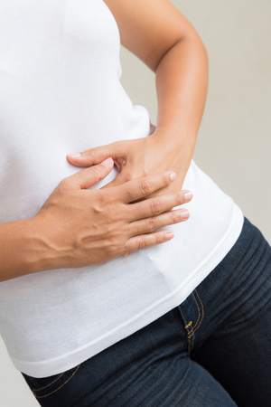 Young woman having painful stomachache. Chronic gastritis. Abdomen bloating concept. Stock Photo