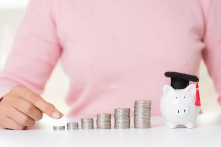 Mano de mujer poniendo moneda de dinero en la pila de monedas y hucha con gorro de graduación en el escritorio blanco. Ahorro de riqueza de dinero para la educación y el concepto financiero.