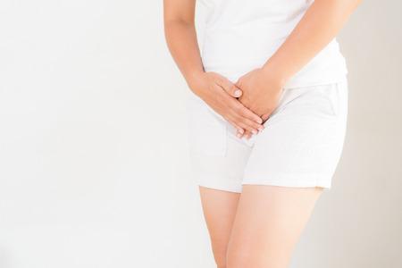Junge Frau, die schmerzhafte Bauchschmerzen mit Händen hält, die ihren Schrittunterbauch drücken. Medizinische oder gynäkologische Probleme, Gesundheitskonzept Standard-Bild