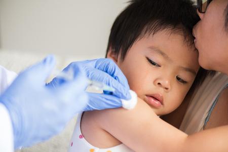 Doctor dando una vacuna inyectable a una niña. Niña llorando con su madre en el fondo. Foto de archivo
