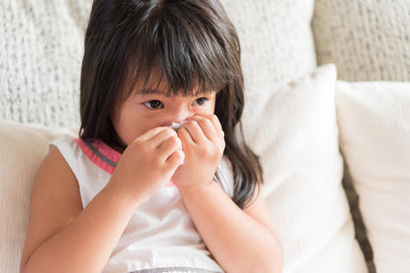 Sick little Asian girl wiping or cleaning nose with tissue sitting on sofa at home. Medicine and health care concept.