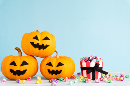Yellow ghost pumpkin with paper star in cup on sky blue background. halloween concept. Stock Photo