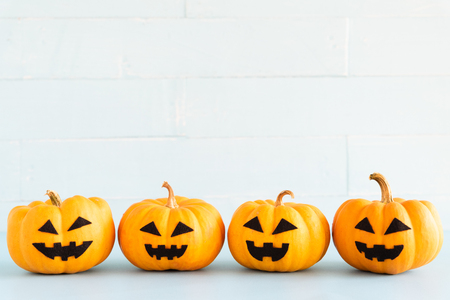 Stack of yellow ghost pumpkin on white brick block background. halloween concept.