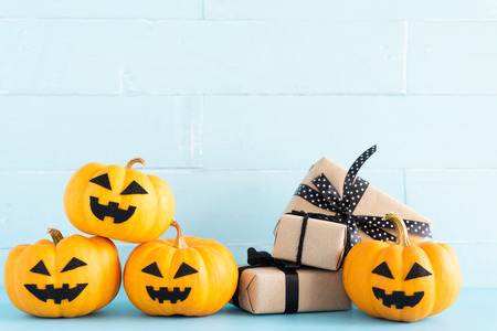 Yellow ghost pumpkin with gift box on cyan wooden background. halloween concept.