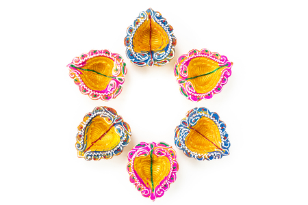 Happy Diwali - Clay Diya lamps lit during Dipavali, Hindu festival of lights celebration. Colorful traditional oil lamp diya on white background Stock Photo