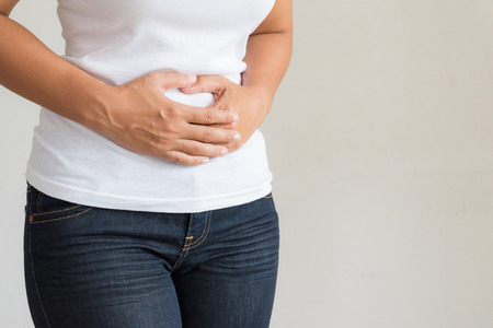 Young woman having painful stomachache. Chronic gastritis. Abdomen bloating concept. Stockfoto