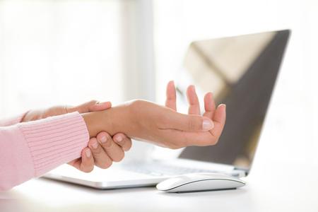 Zbliżenie kobieta trzyma ból nadgarstka od korzystania z komputera. Zespół biurowy ból dłoni spowodowany chorobą zawodową.