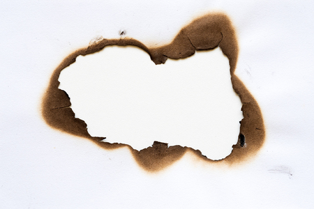 burned hole on piece of paper isolated on white background.